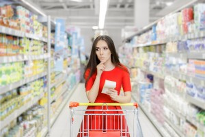 Young girl in red dress in supermarket with a shopping list thinking what to buy