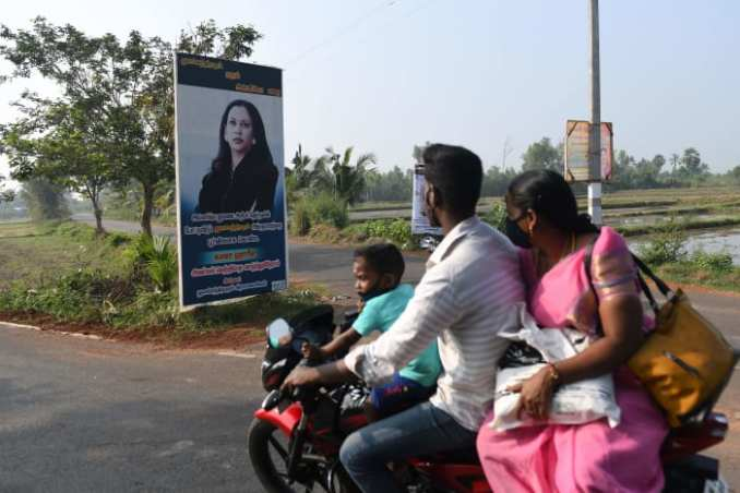 A family rides past a poster of Kamala Harris, displayed on a street at her ancestral village of Thulasendrapuram in the southern Indian state of Tamil Nadu