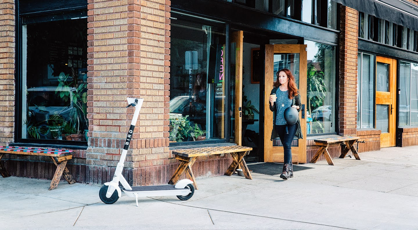 Woman walking out of coffee shop to her parked Bird