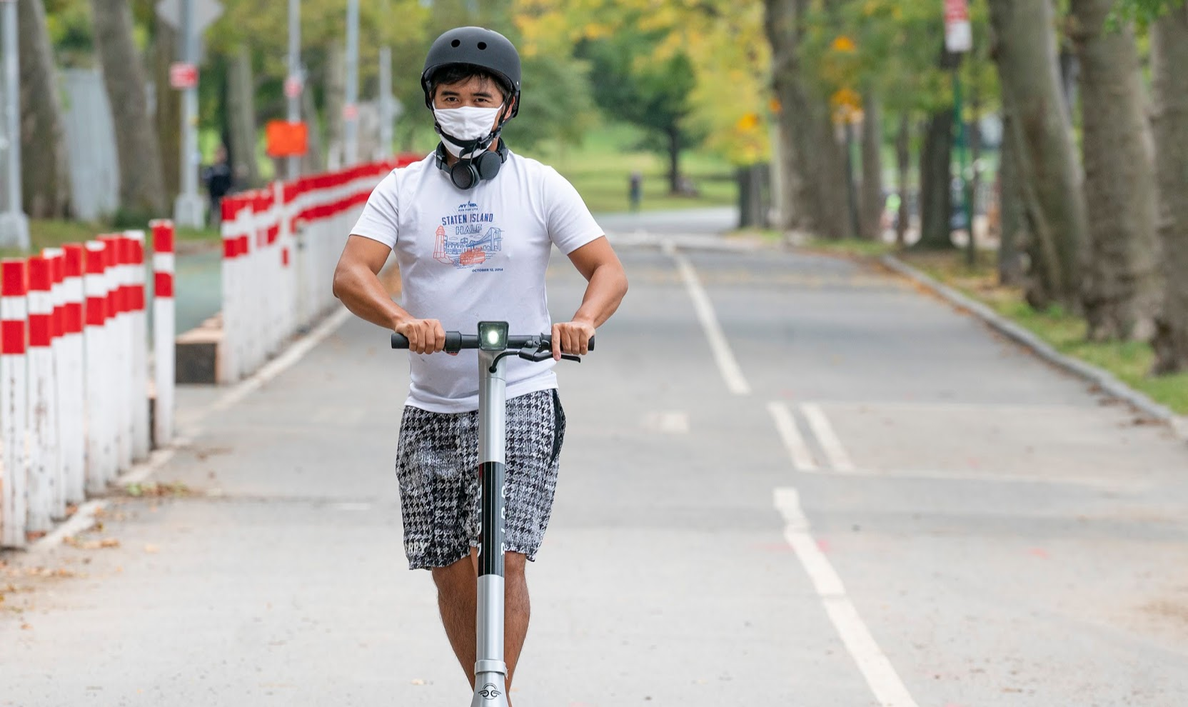 Man rides Bird scooter, wearing helmet and mask