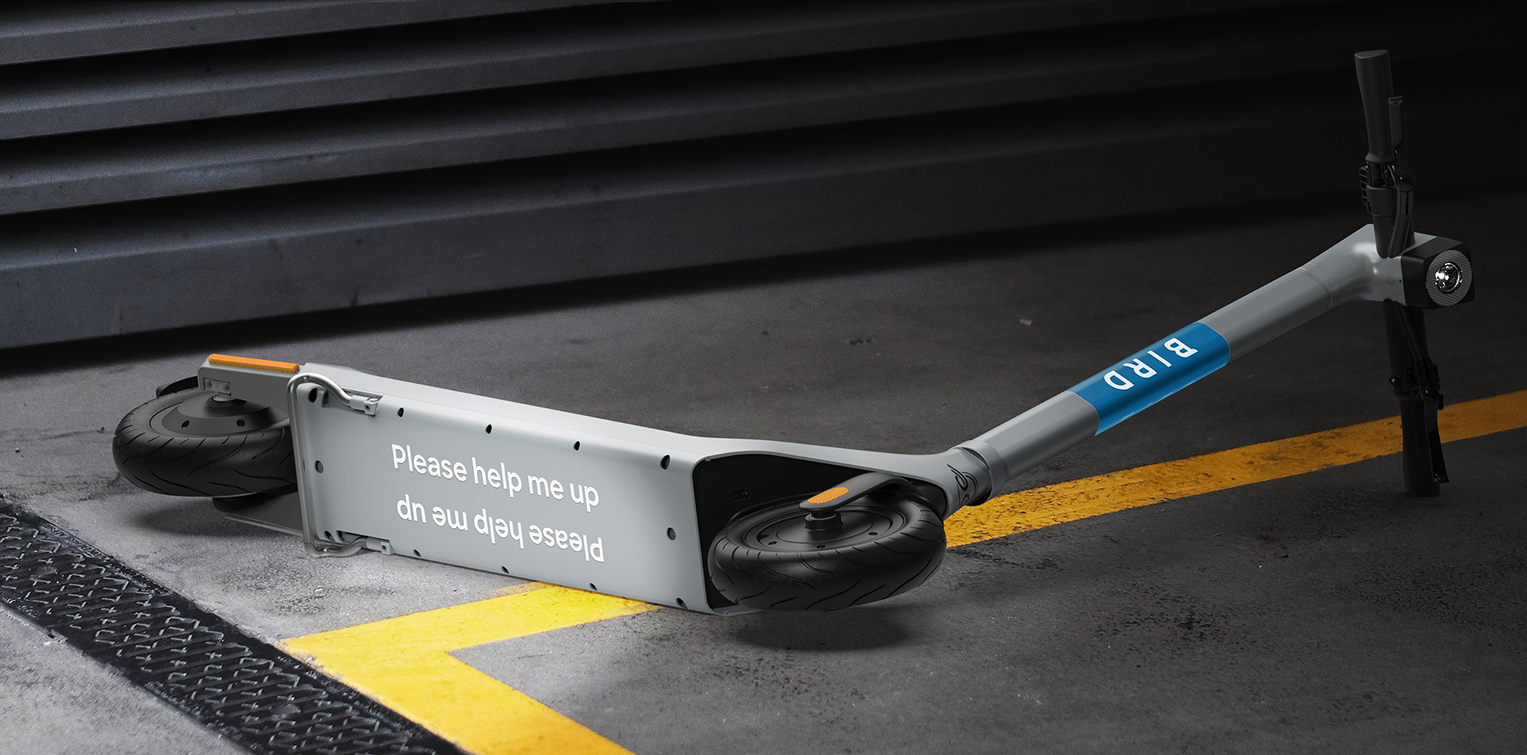 """Image of Bird scooter tipped over with a sticker on the bottom that reads, """"Please help me up"""""""