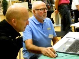 Släktdatas ordförande Hasse Englund hjälper en intresserad släktforskare