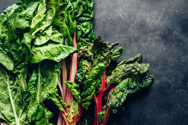 A pile of leafy vegetables with spinach and Swiss chard on a black background