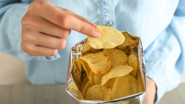 Person in blue button-down eats chips from bag