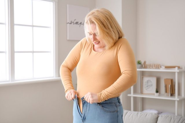 Overweight woman in tight clothes at home trying to fit into tight jeans.