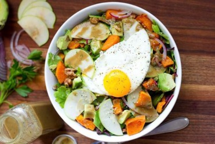 Autumn harvest breakfast salad in a white bowl with diced sweet potatoes and apple slices