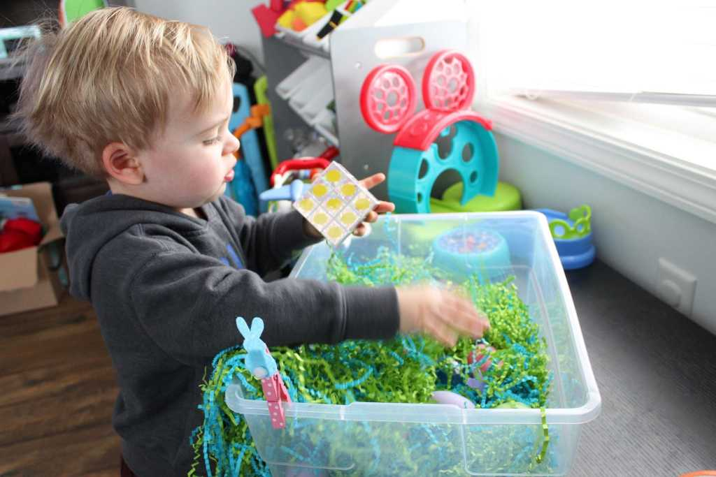 toddler playing with matching cube for bin 1-min