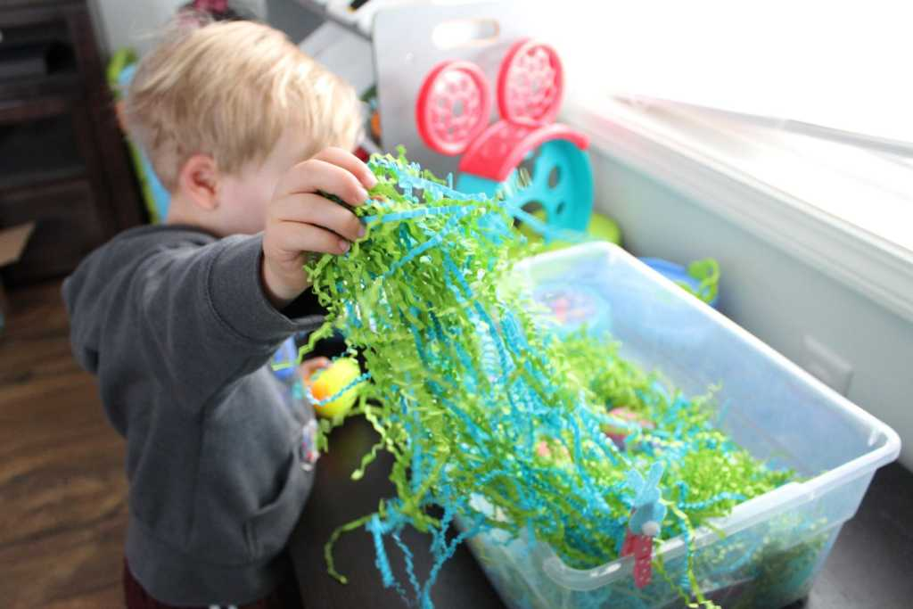 toddler throwing grass out of Easter sensory bin 1-min