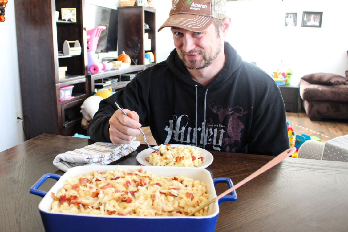 man eating plate of smoked gouda white cheddar bacon macaroni and cheese 1