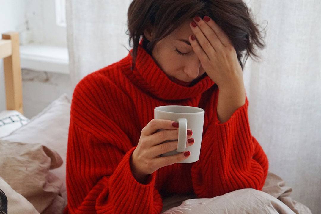 Woman with headache with one hand touching her head and another holding a mug of coffee
