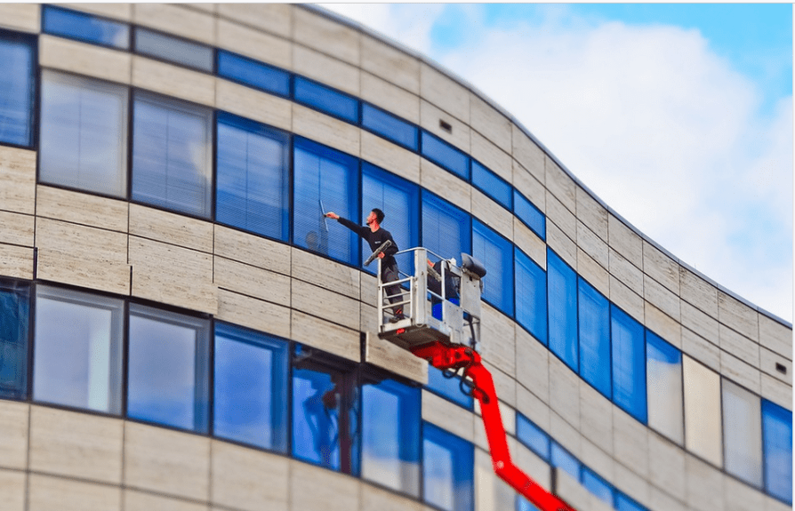 a cleaning company's employee cleaning windows