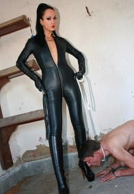 Fetish Liza in Leather Jumpsuit Trains a handcuffed slave in the Stables