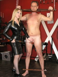 Gorgeous Mistress Sidonia in Latex Dress Plays with a slave in Stocks
