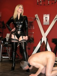 Mistress Sidonia in Latex Puts male slave on a Leash and Pisses on him
