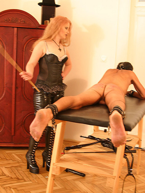Redhead Dominatrix in Boots Tortures and Humiliates a naked hooded slave