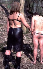 Sexy Domina in Leather Skirt Trashes a slave in the Woods
