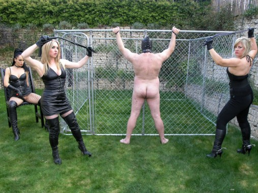 Three Awesome Dominas in Leather Whip and Degrade a hooded slave Outside