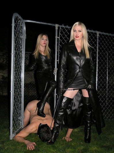 Two Hot Blond Dominas in Leather Coats Discipline a helpless caged slave