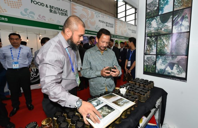 His Majesty looking at wild honey produced by Madu Maangaris, as its owner Firdaus looks on.