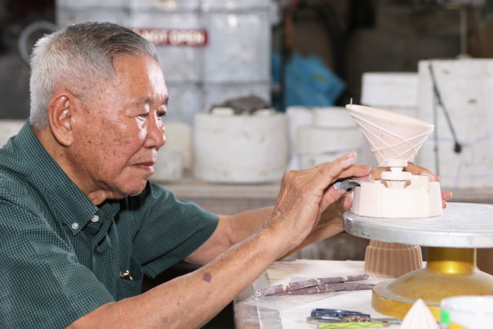 Hj Adnin using sandpaper to smoothen out a ceramic souvenir at Maha Seramik in Mumong. Photos by Faza Suraj.