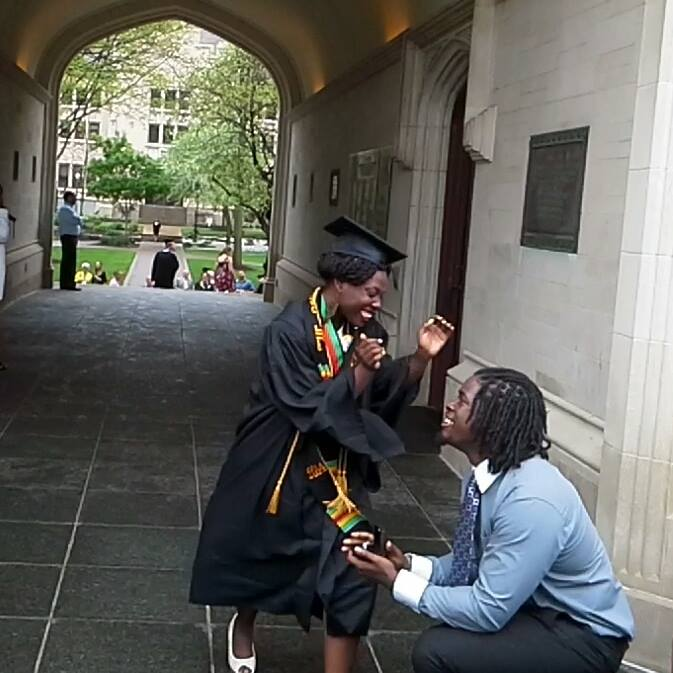 African-American Couple. Man down on one knee proposing to woman. Woman is in cap and gown and is smiling.