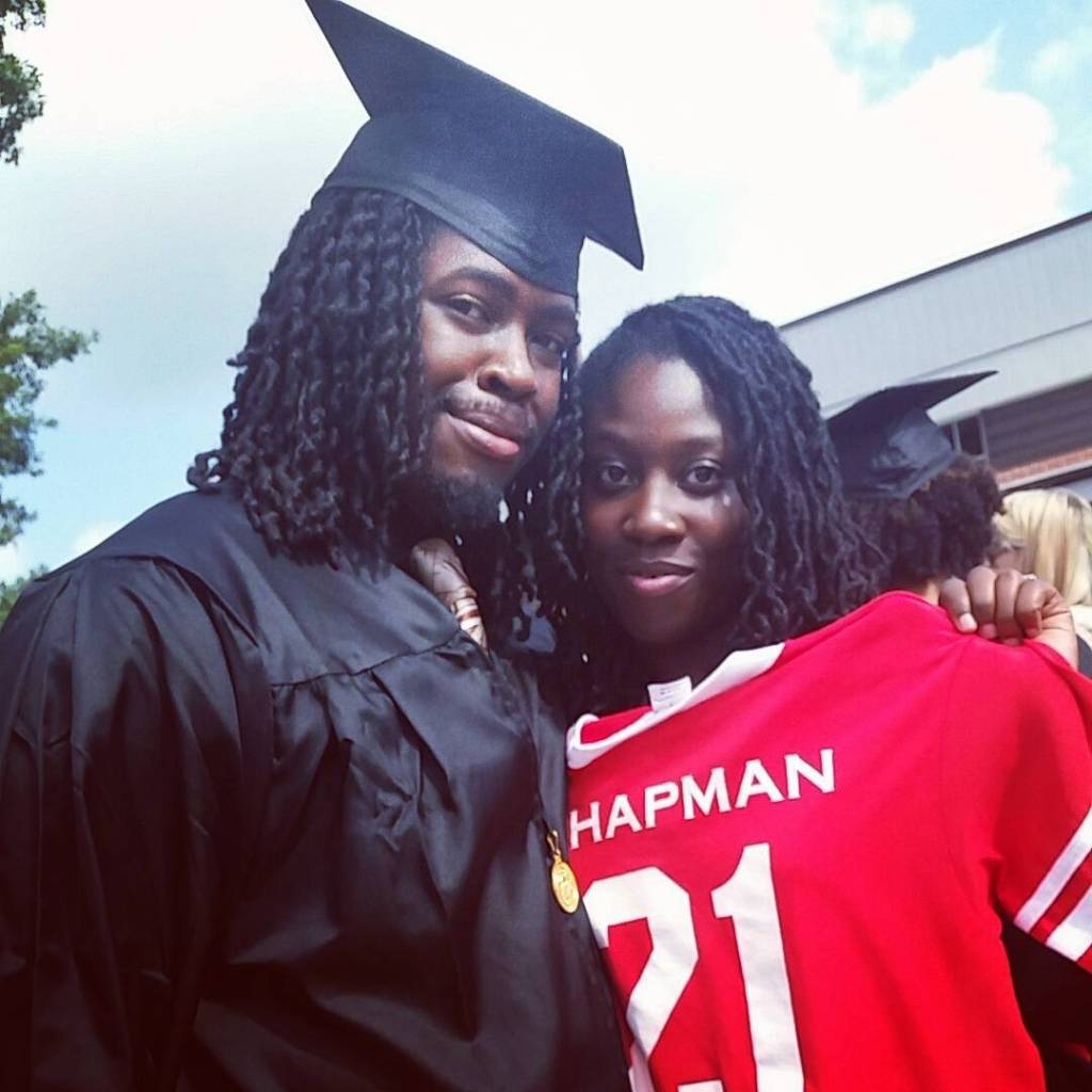 African American man and woman. Man is wearing graduation cap and gown and woman is standing next to him smiling.