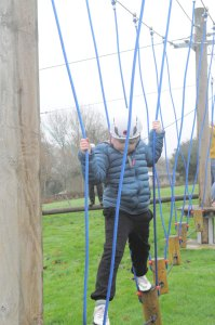 low level ropes course boy crossing stepping logs