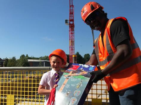 Findlay Clark is presented with gifts by crane driver Manny Marfo on his visit to the Adington site
