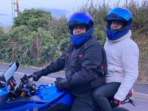 Paul Cowell on his motorbike, with partner Nicola Clark
