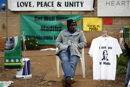 A street vendor sells t-shirts and fabric outside the hospital where ailing former President Nelson Mandela is being treated in Pretoria, July 10, 2013. Credit: Reuters/Mike Hutchings