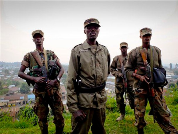 Colonel Makenga, center, commander of the M23 rebel movement, stands on a hill overlooking the border town of Bunagana, Congo, Sunday, July 8, 2012. Rebels have seized several towns in volatile eastern Congo, including Bunagana on Thursday night, and Rutshuru on Sunday. Local official Omar Kavota says the Congolese army looted and fled Rutshuru at the advance of M23 rebels. (AP Photo/Marc Hofer)