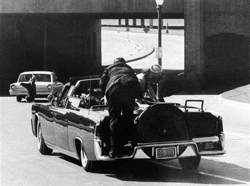 FILE - In this Nov. 22, 1963 file photo, President John F. Kennedy slumps down in the back seat of the Presidential limousine as it speeds along Elm Street toward the Stemmons Freeway overpass after being fatally shot in Dallas. Mrs. Jacqueline Kennedy leans over the president as Secret Service agent Clinton Hill rides on the back of the car. (AP Photo/Ike Altgens, File)