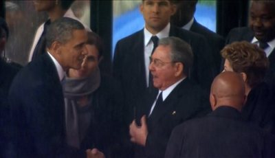 In this image from TV, U.S. President Barack Obama shakes hands with Cuban President Raul Castro at the FNB Stadium in Soweto, South Africa, in the rain for a memorial service for former South African President Nelson Mandela, Tuesday Dec. 10, 2013.  The handshake between the leaders of the two Cold War enemies came during a ceremony that's focused on Mandela's legacy of reconciliation. Hundreds of foreign dignitaries and world heads of states gather Tuesday with thousands of South African people to celebrate the life, and mark the death, of Nelson Mandela who has became a global symbol of reconciliation. (AP Photo/SABC Pool)