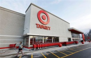 In this Dec. 19, 2013, file photo, a passer-by walks near an entrance to a Target retail store in Watertown, Mass. (AP Photo/Steven Senne, File)