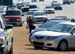 Karen Hurst, left, carries a gas can as she helps Ann Batsun, recover her car on Interstate 75  Thursday, Jan. 30, 2014, in Atlanta. (AP Photo/John Bazemore)