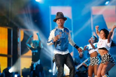"In this Feb. 16, 2014 file photo,  Pharrell Williams rehearses before the NBA All Star basketball game in New Orleans.   The producer-rapper-singer's tune ""Happy"" is nominated for best original song at the Oscars on Sunday, March 2, 2014. Days ahead, the upbeat anthem has climbed to No. 1 on the Billboard Hot 100 chart.  (AP Photo/Bill Haber)"