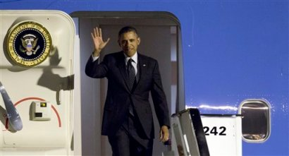U.S. President Barack Obama waves as arrives from Air Force One at Zaventem airport in Brussels on Tuesday, March 25, 2014. (AP Photo/Virginia Mayo)