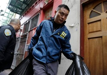 An FBI agent carries away bags of evidence following a search of a Chinatown fraternal organization Wednesday, March 26, 2014, in San Francisco. A California state senator was arrested Wednesday during a series of raids by the FBI in Sacramento and the San Francisco Bay Area, authorities said.  (AP Photo/Eric Risberg)