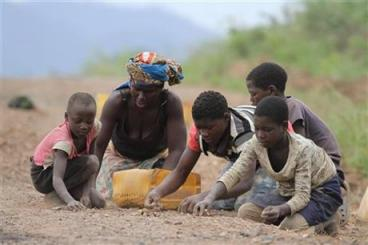 In this photo taken Saturday, Nov. 2, 2013 a a woman and children separate stones from roadside sand to sell as building material in Inchope, northern Mozambique. (AP Photo/Tsvangirayi Mukwazhi)