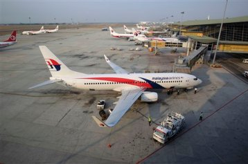 Ground staff work on a Malaysia Airlines plane at Kuala Lumpur International Airport in Sepang, Malaysia, Wednesday, March 12, 2014. (AP Photo/Lai Seng Sin)