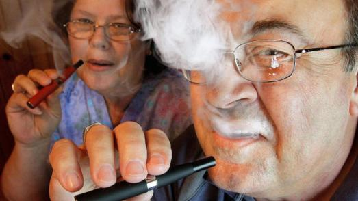 In this May 31, 2011 file photo, Cliff Phillips, a 61-year-old retiree and former smoker, and his wife, Vali, enjoy electronic cigarettes at their home in Cuba, Ill. (AP Photo/Seth Perlman, file)