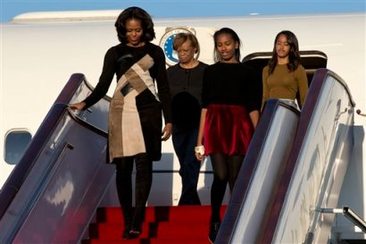 U.S. First Lady Michelle Obama, front left, her daughters Sasha, front right, Malia, right in the back, and Michelle Obama's mother Marian Robinson, left in the back, arrive at Capital International Airport in Beijing, China, Thursday, March 20, 2014. (AP Photo/Alexander F. Yuan, Pool)
