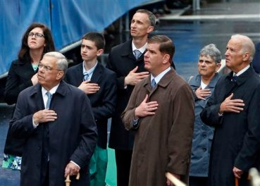 From right, U.S. Vice President Joe Biden, Boston Mayor Marty Walsh, and former Boston Mayor Thomas Menino, react along with the family of Boston Marathon bombing victim Martin Richard, behind, during a remembrance ceremony at the finish line on Boylston Street in Boston, Tuesday, April 15, 2014. (AP Photo/Elise Amendola)