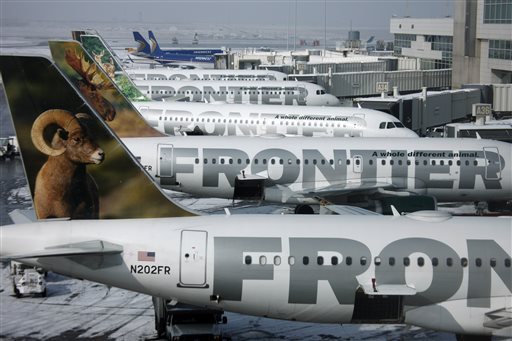 In this Feb. 22, 2010 file photo, Frontier Airlines jetliners sit stacked up at gates along the A concourse at Denver International Airport. Passengers flying Frontier Airlines will now have to pay extra to place carry-on bags in overhead bins or for advance seat assignments. The move comes as the Denver-based airline transforms itself into a fee-dependent airline, similar to Spirit Airlines or Allegiant Air _ the only other U.S. carriers to charge such fees. (AP Photo/David Zalubowski, File)