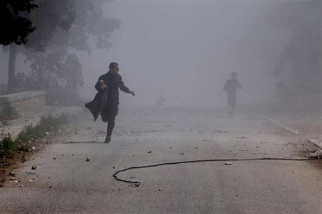 In this photo provided by the anti-government activist group Aleppo Media Center (AMC), which has been authenticated based on its contents and other AP reporting, Syrian residents run in the street after a government warplane dropped barrel bombs at al-Sakhour neighborhood, in Aleppo, Syria, Saturday, April 5, 2014. The leader of al-Qaida, Ayman al-Zawahri , called on Syrian militant groups to determine who killed his representative in the country, a man many fighters believe died at the hands of a rival militia. (AP Photo/Aleppo Media Center, AMC)