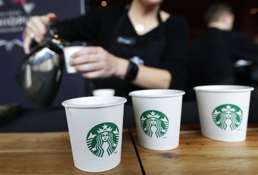 In this March 19, 2014 file photo, Sandy Roberts, Starbucks strategy manager for global coffee engagement, pours samples of coffee for shareholders and other guests, at Starbucks' annual shareholders meeting in Seattle. Starbucks reports quarterly earnings on Thursday, April 24, 2014. (AP Photo/Ted S. Warren, File)