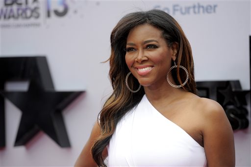 "This June 30, 2013 file photo shows TV personality Kenya Moore at the BET Awards in Los Angeles. Moore says she's seriously considering leaving ""The Real Housewives of Atlanta"" after her televised brawl with co-star Porsha Williams. Williams surrendered last week to authorities and was charged with a misdemeanor charge of battery for the fight, which was televised as part of the Bravo show's reunion special on Sunday, April 20. (Photo by Chris Pizzello/Invision/AP, File)"