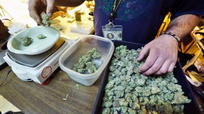 An employee weighs portions of retail marijuana to be packaged and sold at 3D Cannabis Center in Denver, Dec. 31, 2013. (Brennan Linsley/AP Photo)