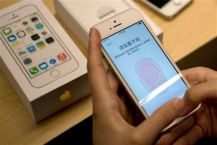 In this Sept. 20, 2013 file photo, a customer configures the fingerprint scanner technology built into iPhone 5S at an Apple store in Beijing. (AP Photo/Andy Wong, File)