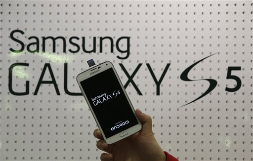 In this March 27, 2014 file photo, an employee shows Samsung's Galaxy S5 smartphone at a mobile phone shop in Seoul, South Korea. Samsung's new Galaxy S5 smartphone is more durable than last year's model and other leading Android phones, but the iPhone 5s outperformed all of them in part because of its smaller size, a new study finds. (AP Photo/Lee Jin-man, File)
